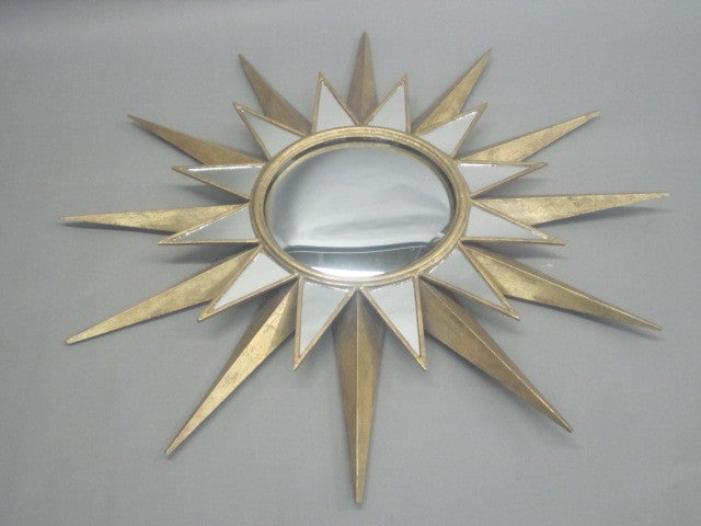 Pair of large elegant sunburst/starburst mirrors in gilt iron with inlaid mirrored pieces. Center mirror is convex in form. 