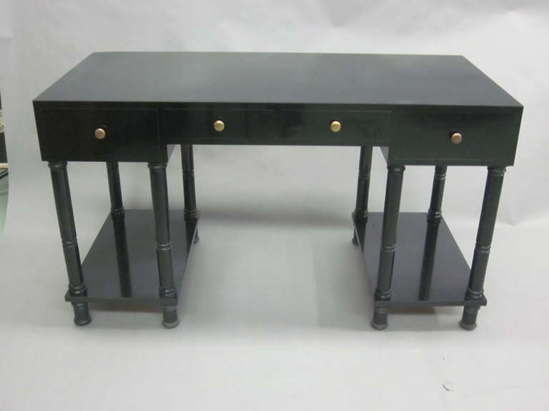 Elegant French midcentury desk or writing table in the modern neoclassical taste by Maison Jansen with a black lacquer base and black laminate top and four drawers.  The desk top is supported by 4 simply rusticated legs on each side and united by