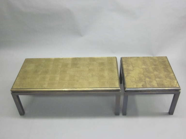 A set of two French Mid-century Modern coffee tables that form one long table: Each with reverse painted glass top that has been hand gilt in the form of squares. Designed by Guy Lefevre for Maison Jansen with inspiration from a sober, modern
