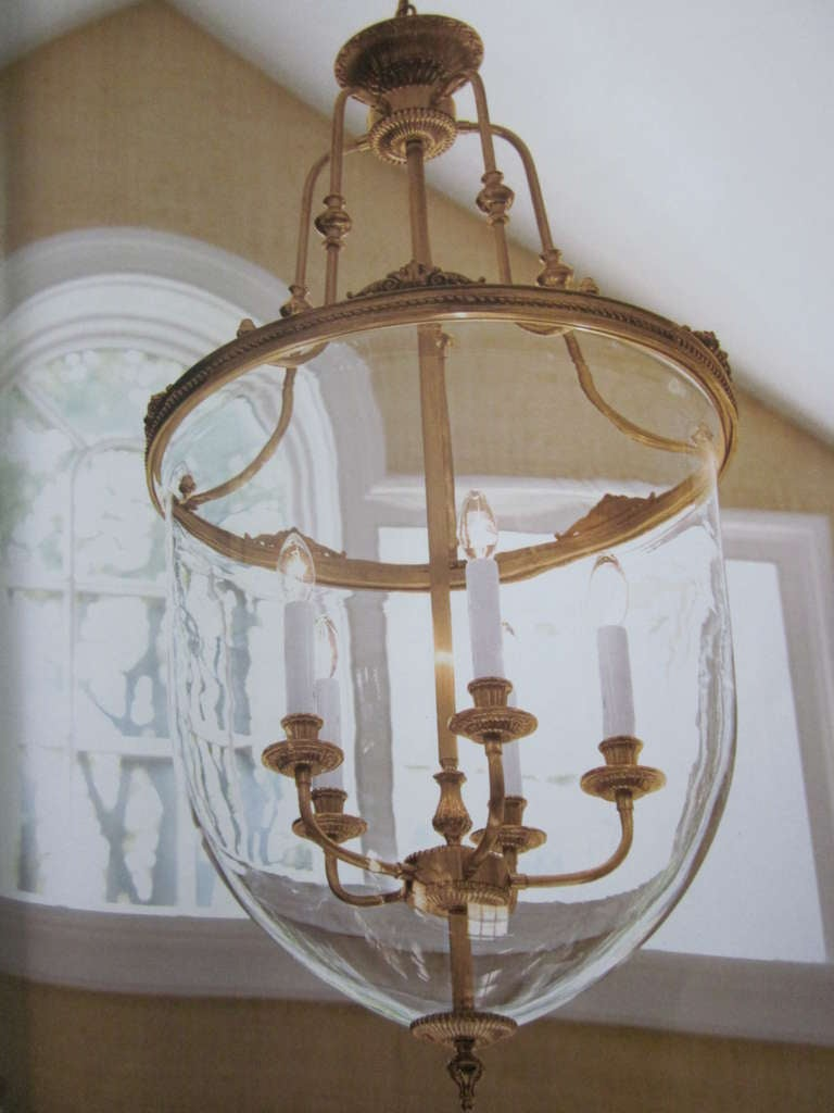 Two pairs of French Mid-Century Style Modern Neoclassical lanterns / pendants / chandeliers. Sober, elegant with the highest quality materials and workmanship, handcrafted gilt solid brass frames and armature with mold blown curved glass.   One pair