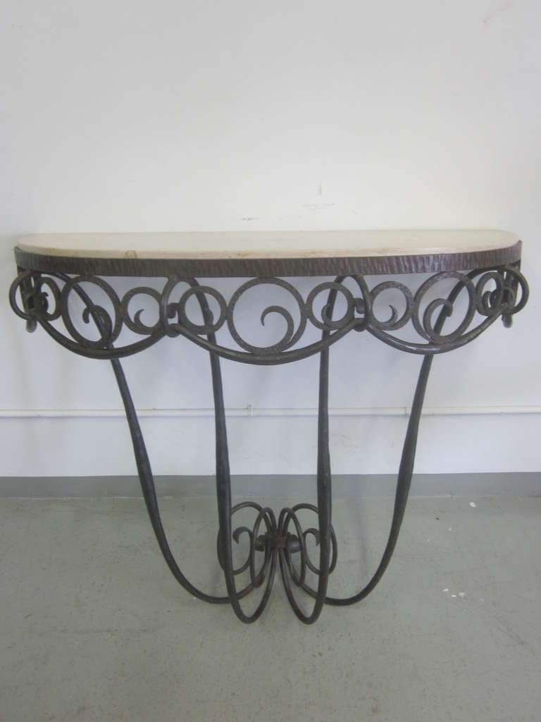 An exquisitely hand-hammered French Art Deco wrought iron wall console by Edgar Brandt with an inset demilune top of jura limestone.  The piece is delicately hammered with the iron forming a rhythmic flowing pattern both at the base and apron. A