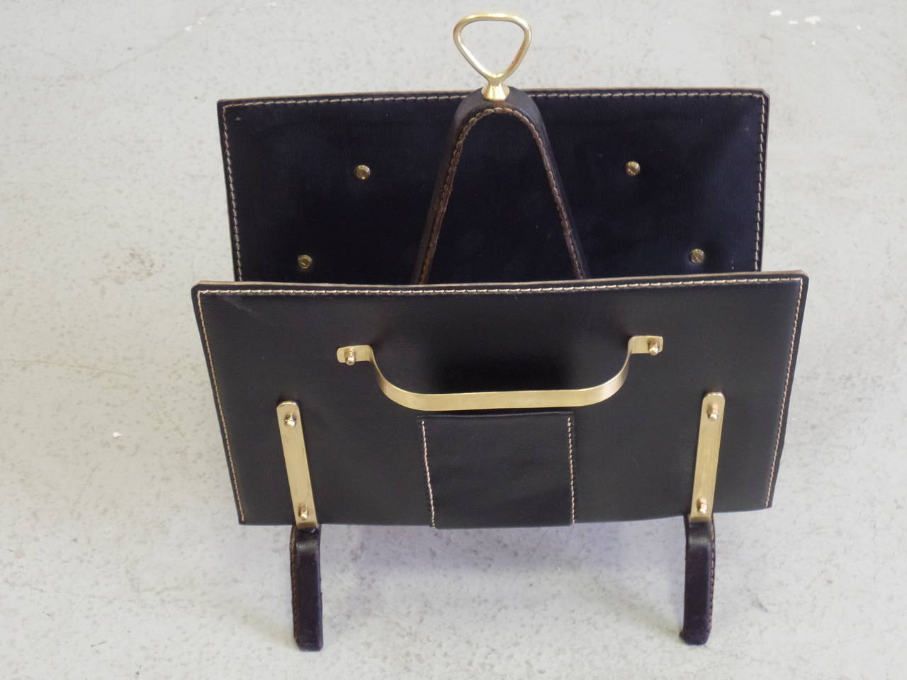 Elegant and timeless French Mid-Century Magazine rack or stand in a sober, modern spirit by Jacques Adnet. The piece is composed of black hand-stitched leather and the composition and color balance are completed by solid brass detailing. In