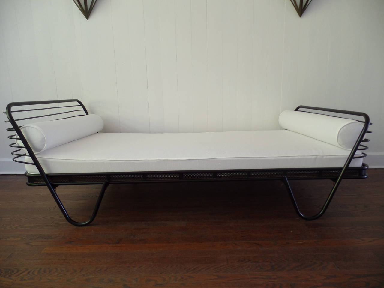 An elegant French Mid-Century Modern day bed, single bed or chaise lounge known as 'Kyoto' by Mathieu Matégot. The stunning black enameled iron frame emphasizes transparency with a perforated metal apron holding the mattress and two headboards in a