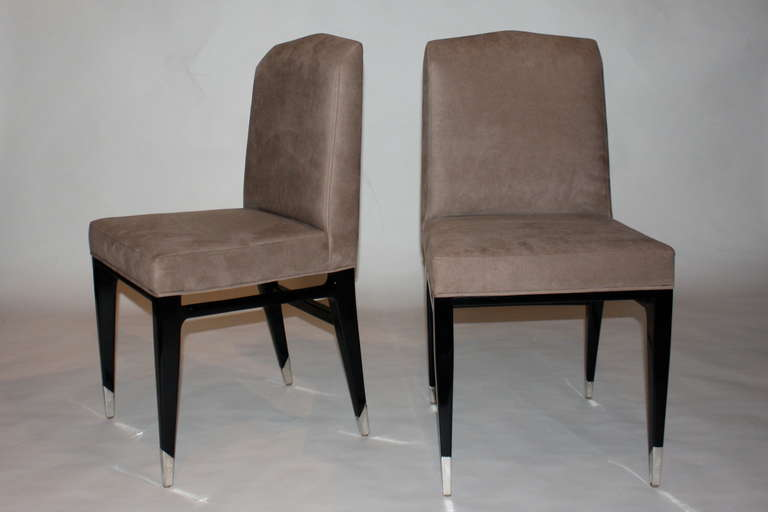 Elegant chairs finished in black lacquer on silver plated sabots.
