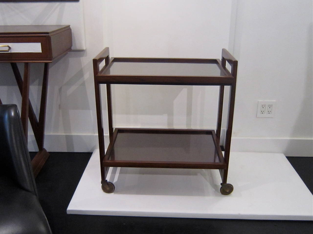 Mid-Century mahogany bar cart by Andre Sornay with studded brass details on the sides and glass inlaid tops.
