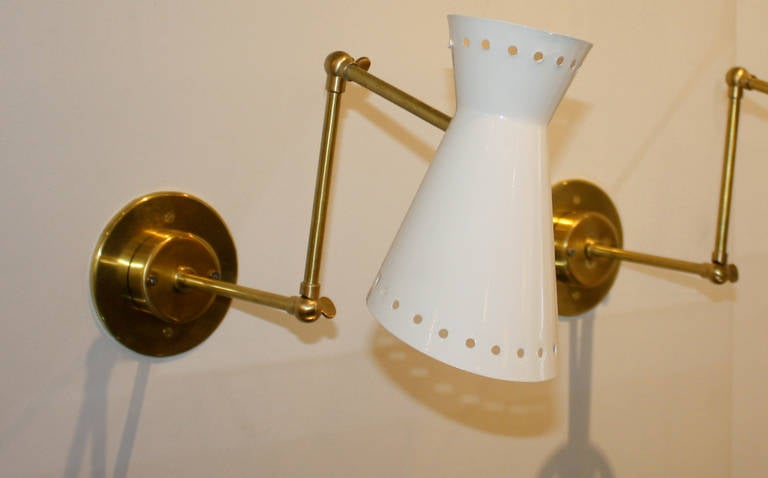 """Perforated metal shade sconces with articulated brass arms. The arms are articulated in two points for various positions. Round brass backplate with white powder coated shades. Measures: Full length: 23"""", articulated length (pictured) 18""""."""