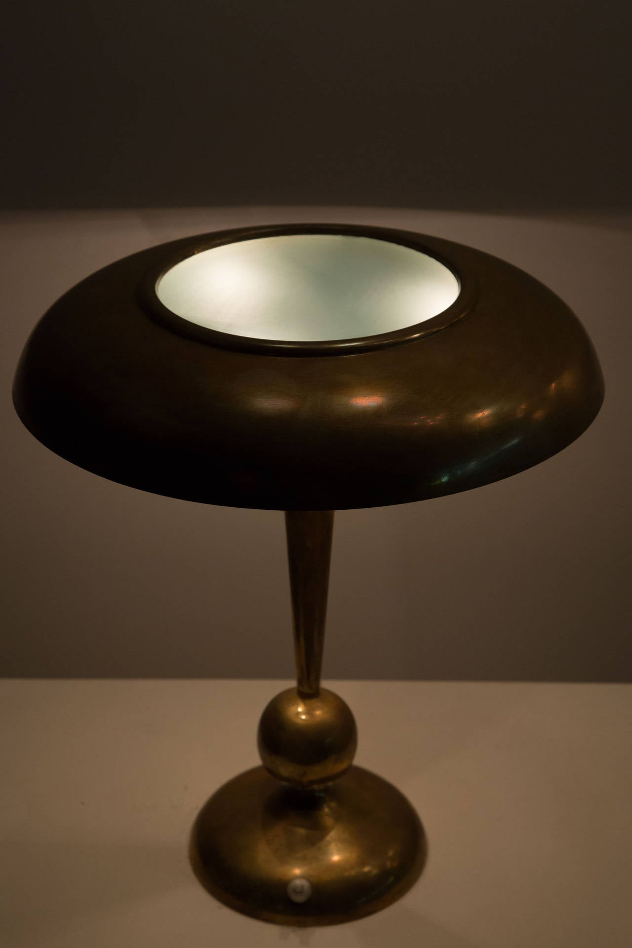 Brass table lamp with tilt swivel ball joint at base.