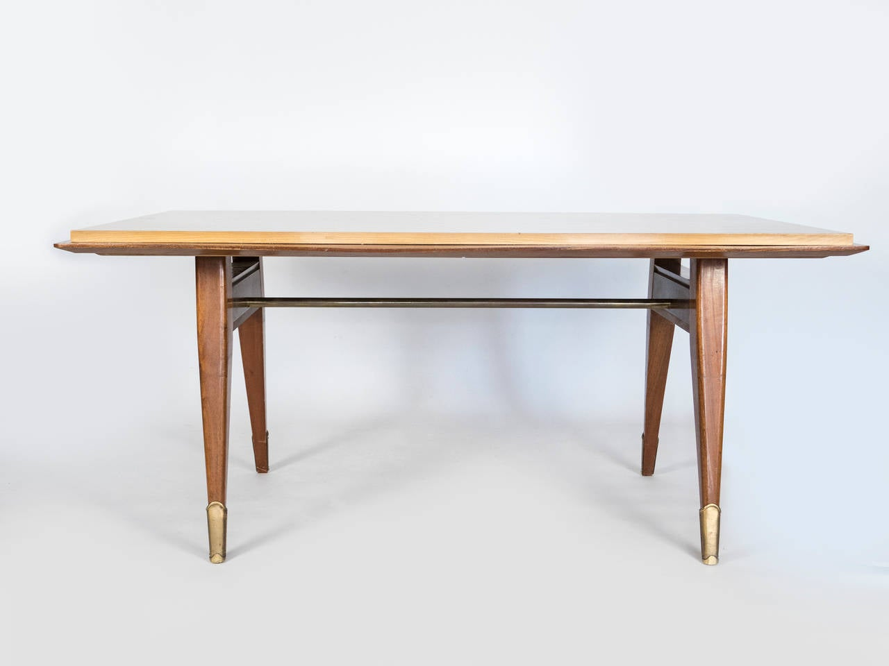 This table with its mahogany base and sycamore table top has a unique design.   the brass elements accentuate the legs and the cross bar.  Comfortably seats six people.