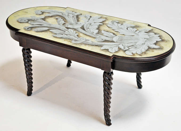 1940s coffee table made by Grosfeld House. Carved wood base with inset églomisé glass top. The back of the glass is decorated with antique silver leaf. The result is a mirror-like, reflective finish with black shadowing and cream background.