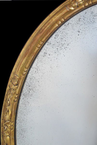 An elegant pair of French Napoleon III carved giltwood oval mirrors; each half-round moulding with floral and foliate carved reserves surrounding a beaded inner slip.