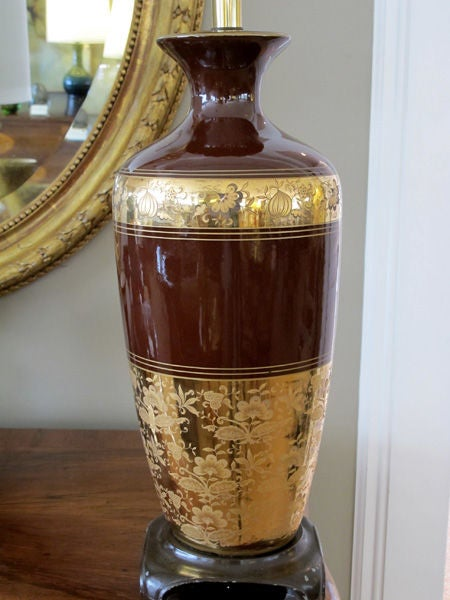 A richly-colored pair of American 1960s chocolate-brown ceramic lamps with fine gilt decoration; each with flaring neck above a tapering body; adorned with gilt perimeter bands depicting delicate meandering floral vines; raised on a metal base with