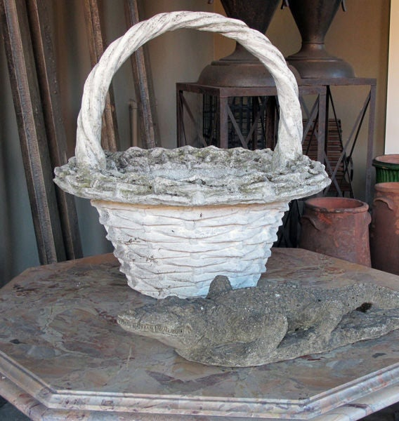 A boldly-scaled French faux basket-weave concrete jardiniere with arching handle; the tall braided handle joining a tapering body of a simulated weaved basket