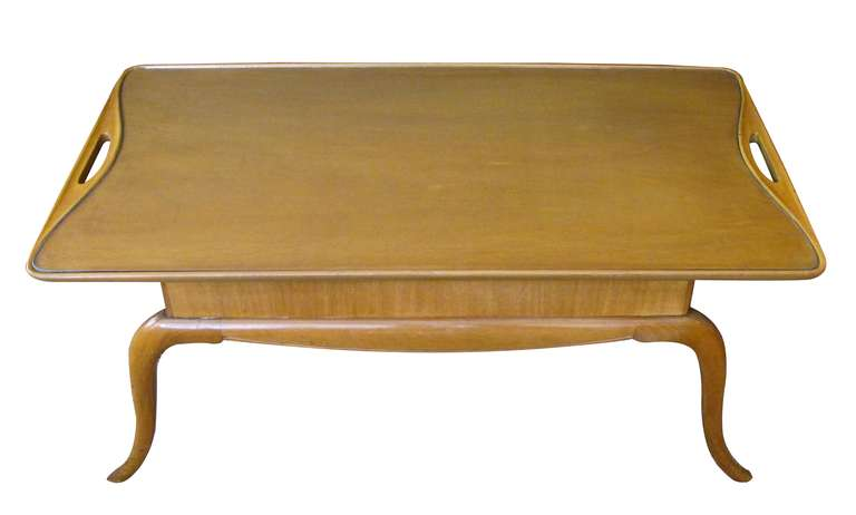 A chic and stylish Italian midcentury pearwood cocktail table with graceful splayed legs; the rectangular top with glass inset flanked by open handles; over a thick apron raised on elegant splayed supports.