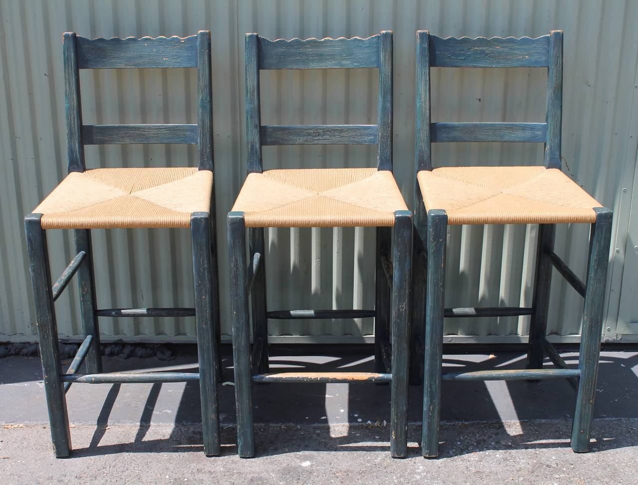 This set of three matching original blue painted handmade bar stools are in good as found condition. The stools are ladder back style with newly hand woven rush seats. Fantastic look for Spanish or country house. They were from a wine cellar or bar