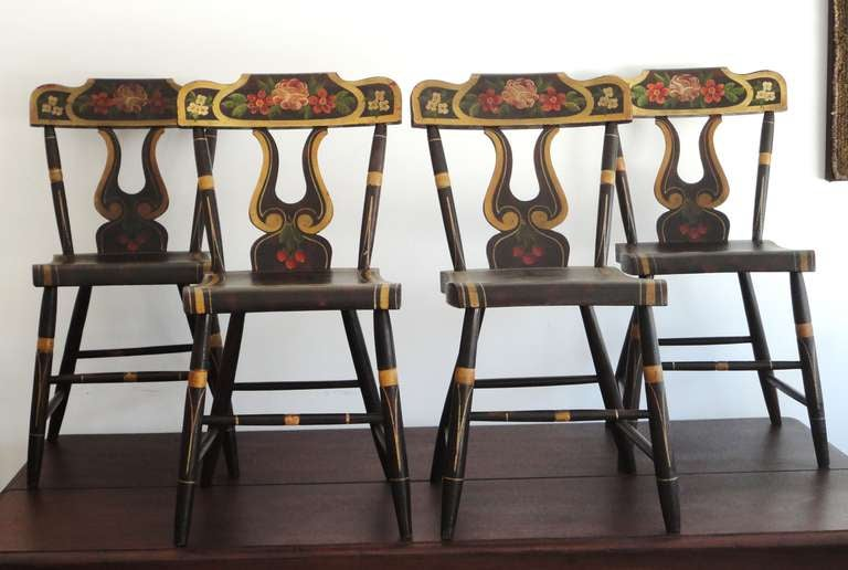 Early and all original colorful 19thc decorated plank bottom chairs from Lancaster County ,Pennsylvania .The untouched remarkable painted surface and form is the very best.These lire cut out backs are also heavily  decorated along with the seat back