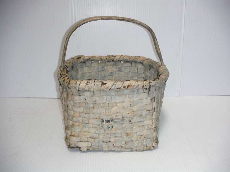 This original 19th century cream or dirty white painted gathering basket was found in New England and is very heavy in weight from the thick splint and coats of paint. The surface is fantastic and has a wonderful untouched patina. There are some