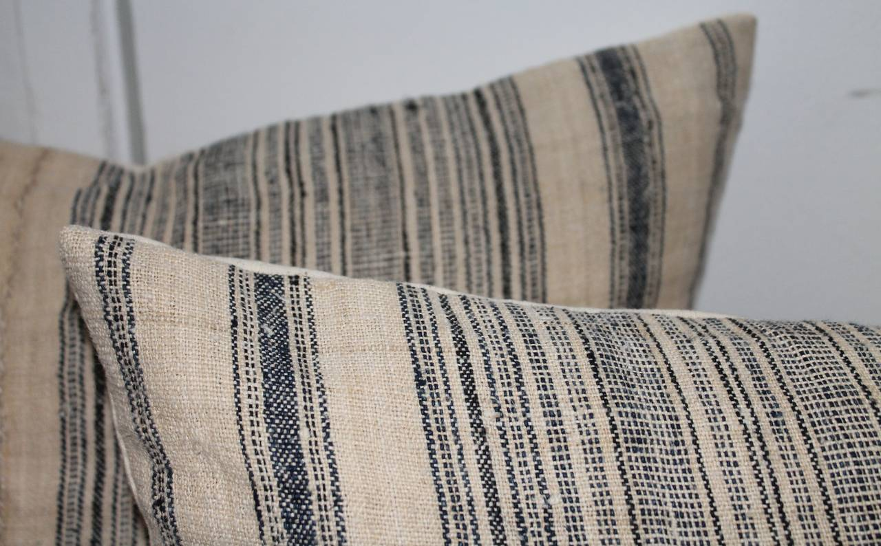 Early 20th century blue and cream linen ticking pillows. These ticking pillows are in excellent condition. The beautiful chain like strains of blue and crème are done with expert precision. This item has some wear which is consistent with age. The
