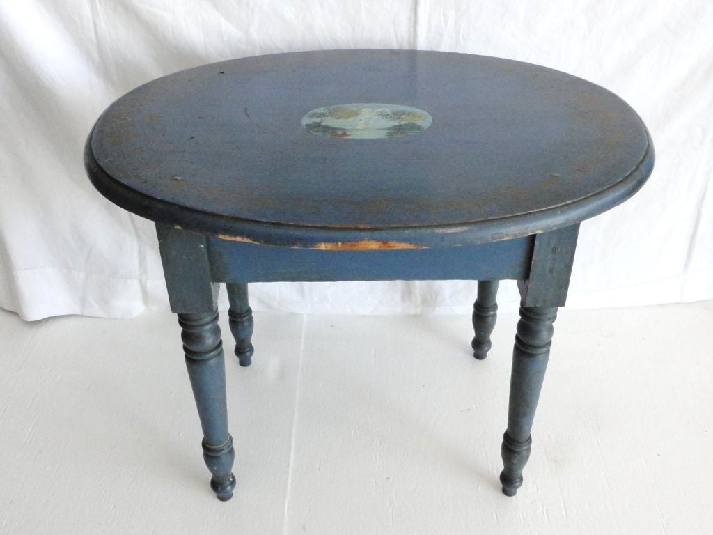 19th century blue painted small oval table with original decoration of a New England scene in the center of the tabletop. This table has fantastic gilded stencil around the edge of the table throughout the tabletop. This little painted decorated