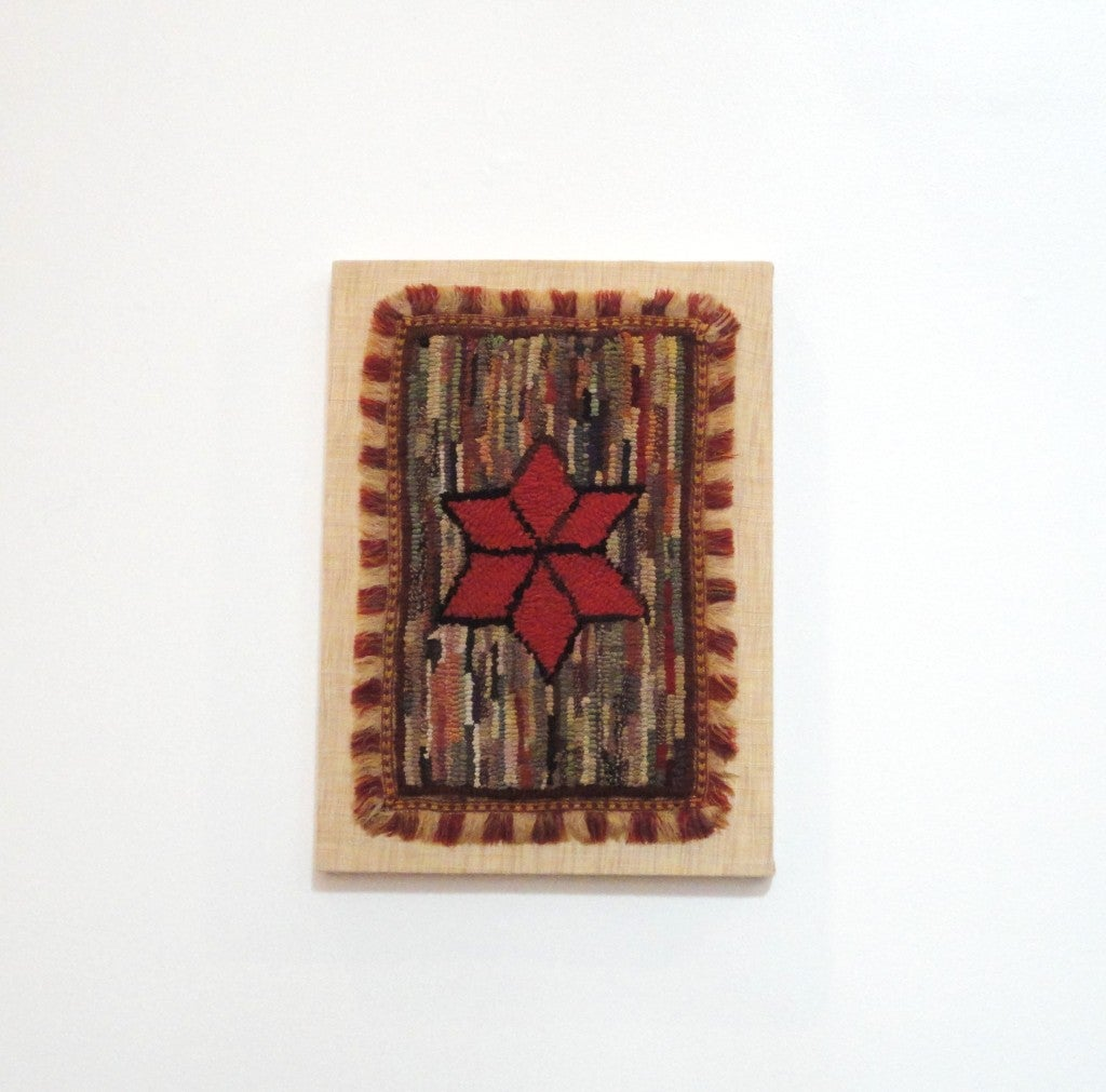 This wonderful little early American hand-hooked miniature rug with original fringe is professionally mounted. This is such a very unusual example of Folk Art and in a hit or miss pattern with a center star motif. The fringe is another added rarity