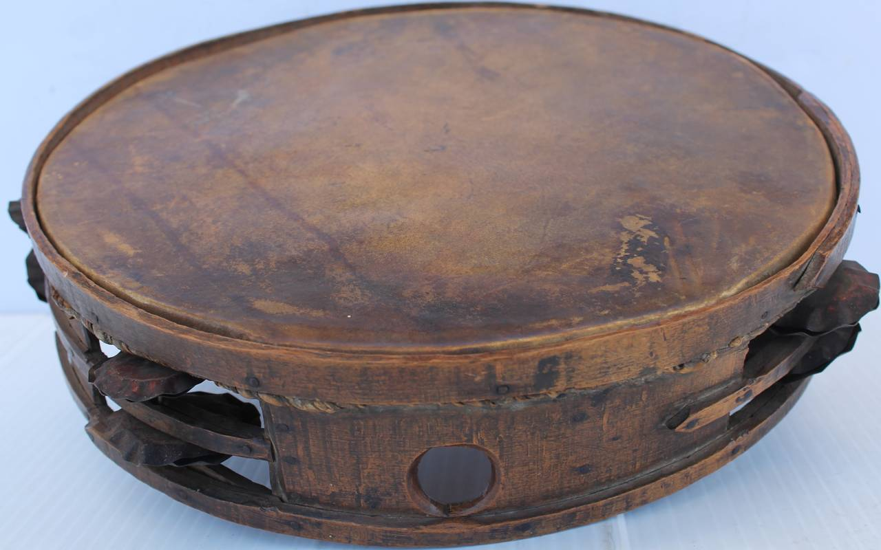 This early 19th century tambourine is all handmade and wonderful finger bands construction throughout. This early tambourine has hand cut tin shakers and is all constructed with early cut nails. The raw hide drum like top is original hide with a