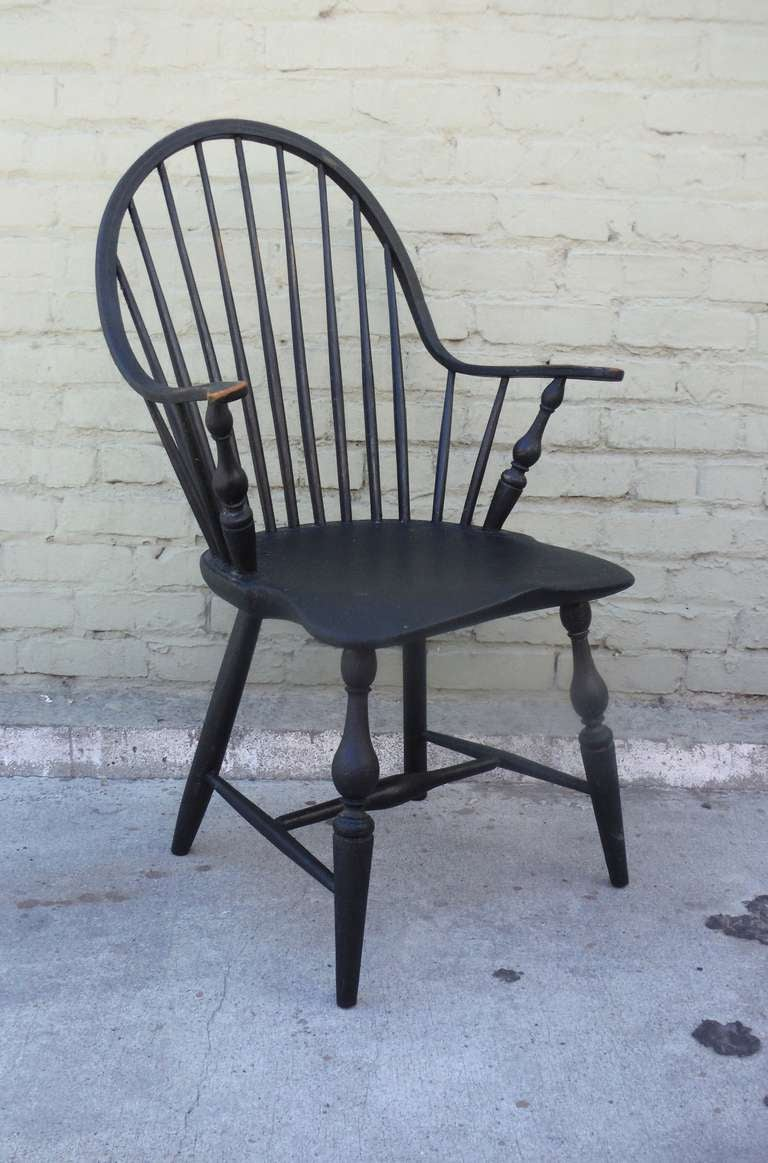 """This 18th century New England continuous arm Windsor chair is a spectacular example of early American furniture design.  With all original black paint and untouched surface , this chair was constructed from one """"continuous"""" piece of wood that was"""