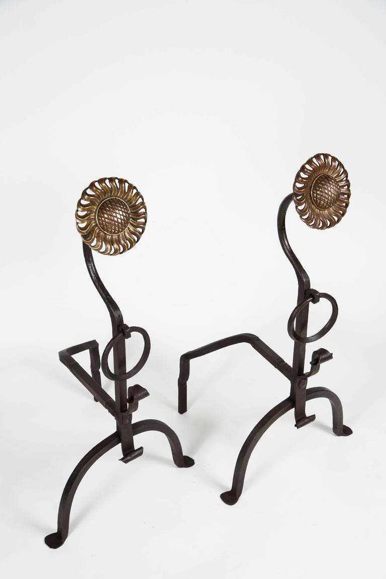 A pair of hand-forged iron Arts & Crafts andirons topped with decorative brass sunflower rosettes.