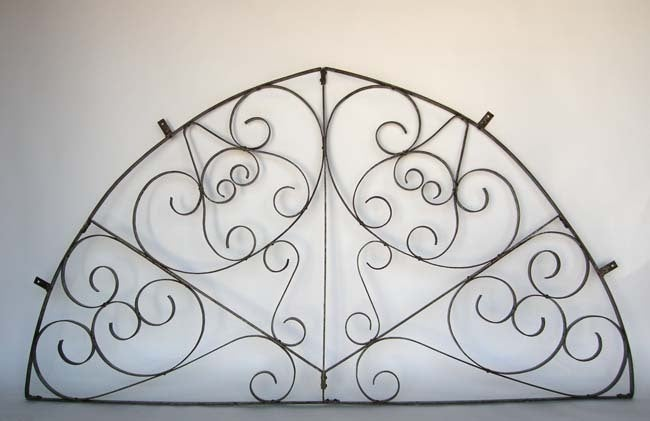 19th c. large iron architectural fragment  with scroll work.  Was originally used as a window grill in Guatemala.  Has original brackets which create space from the wall and casts shadows and gives it dimension .