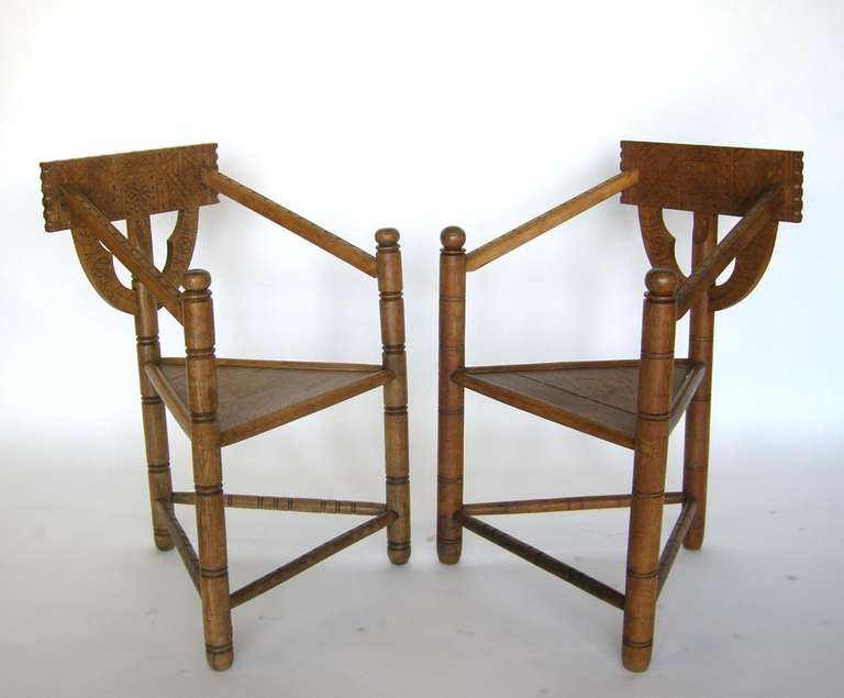 Antique triangular monk chairs in oak with carved chair backs on both sides. Late 19th & Swedish Monk Chairs