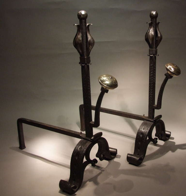 A pair of large and substantial Art and Crafts andirons in wrought iron with polished finials in the form of stylized tulips over etch decorated shafts having large spit supports with contrasting bronze suppressed ball finials.