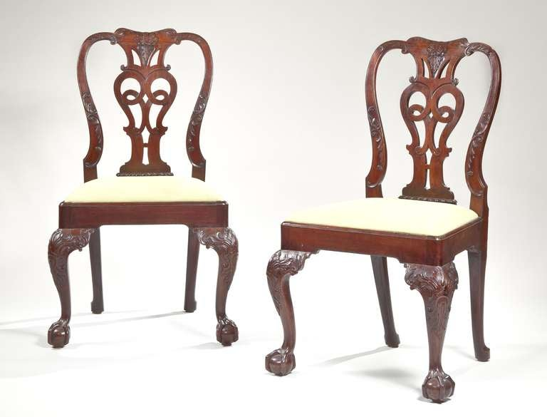 A superb set of eight George II carved mahogany dining chairs having a carved crest rail with a pierced and carved splat, carved styles, having a drop in seat on substantial carved cabriole legs terminating in ball and claw feet. 