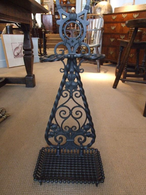 A cast iron umbrella stand by noted maker Bradley and Hubbard, having elaborate scrollwork decoration, twist holder and carrying handle, with wonderful beaded base pan.