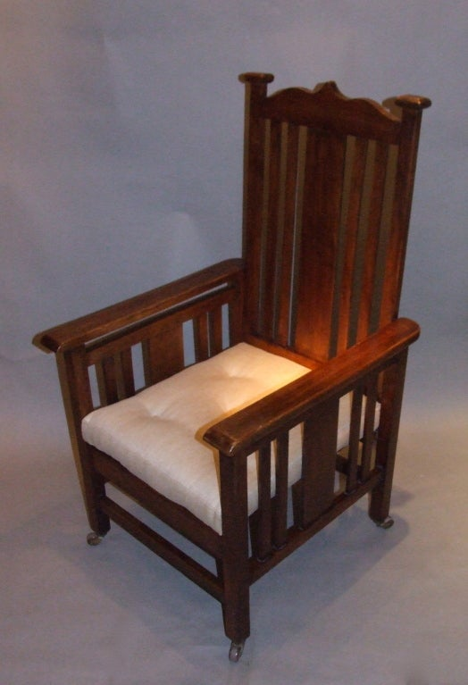 Good English Arts and Crafts period armchair, the shaped crest over slatted back, the arms similarly slatted, standing on square legs on original brass and ceramic castors, the upholstered cushion with shallow button tufting, the whole with good