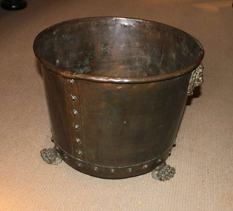 Good English 19th Century copper and brass log holder or planter having a rolled lip and hand hammered and riveted body, the lion masks and paw feet in brass, the whole with mellow patina and slight verdigris surface.  vessel, log bin, bucket,