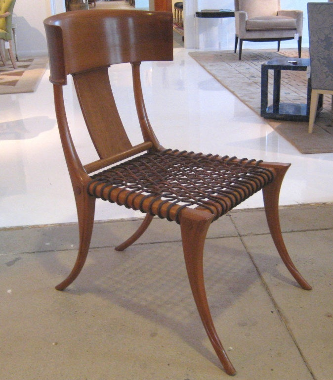 Greek walnut and leather strapped side chair with graceful curving back and exaggerated sabre legs. A modern interpretation of seating depicted on ancient pottery. With metal label and additional label indicating this was originally part of a set,