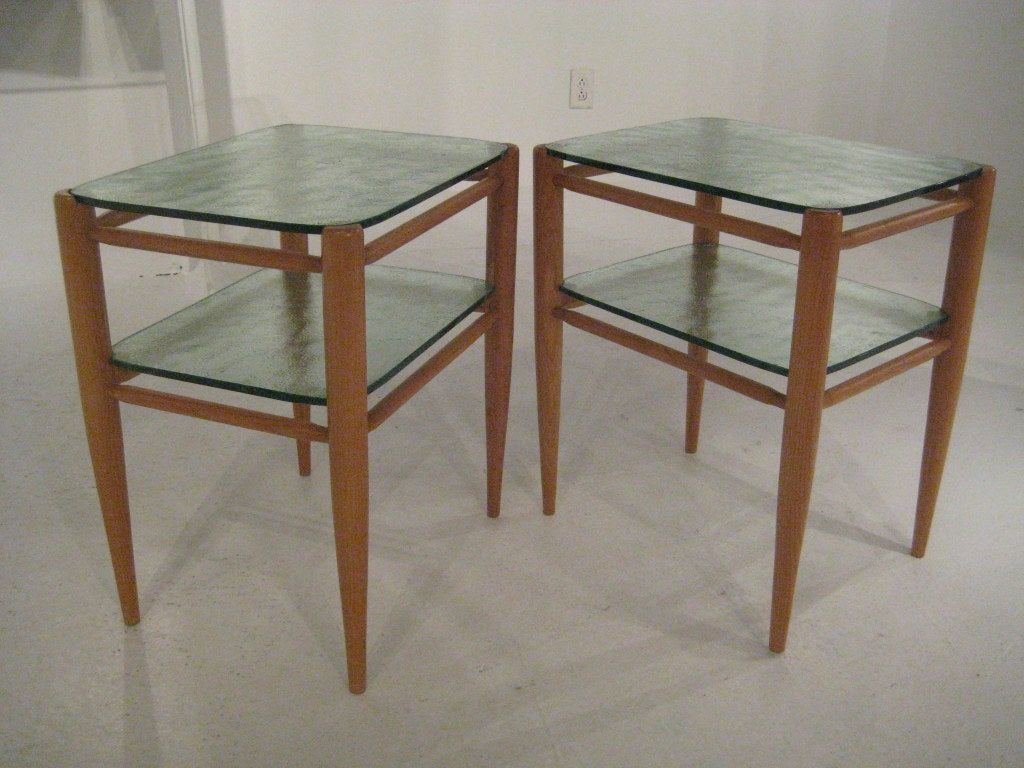 Custom two-tier oak dowel tables with 1/2 inch textured glass shelves. The simple designs belies marvelous construction technique such as invisible inset shelf supports, and each glass pane custom cut to fit its shelf.