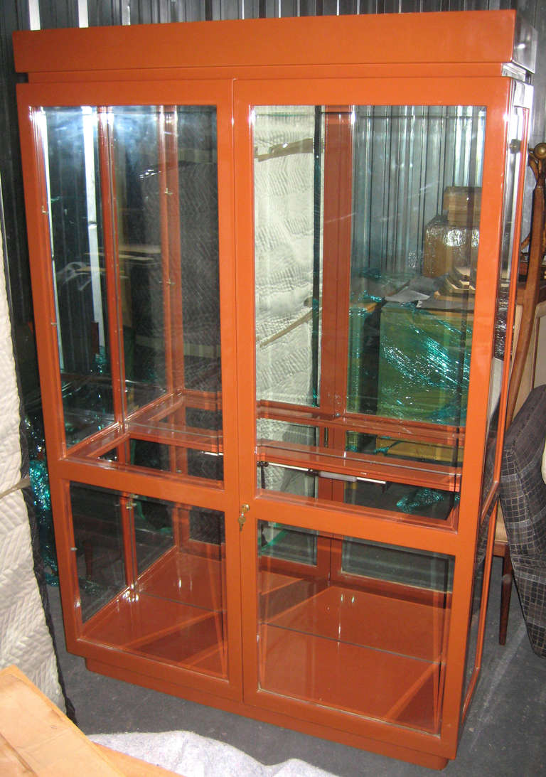 Wonderful orange lacquered vitrine with glass doors and shelves mirrored back, top and middle display lights, and brass hardware. Four adjustable glass shelves originally acquired through the Duquette Studio estate sale in 2000. Pencil signed