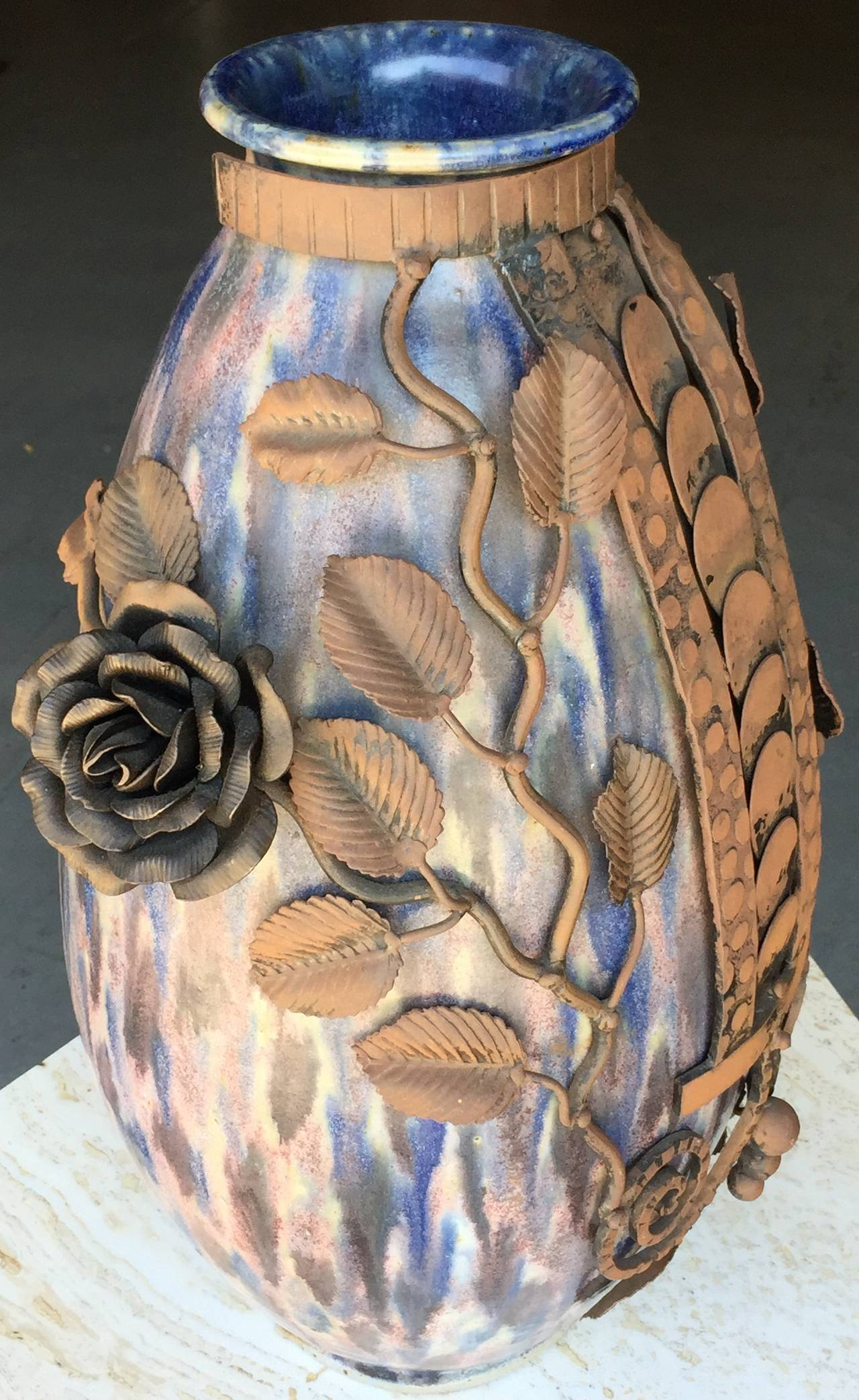 Large hand thrown pottery vase by Roger Guerin with subtle poly-chromatic glaze, with elaborate hand-chased wrought iron applique´ by Franc¸ois Carion. Signed on bottom.