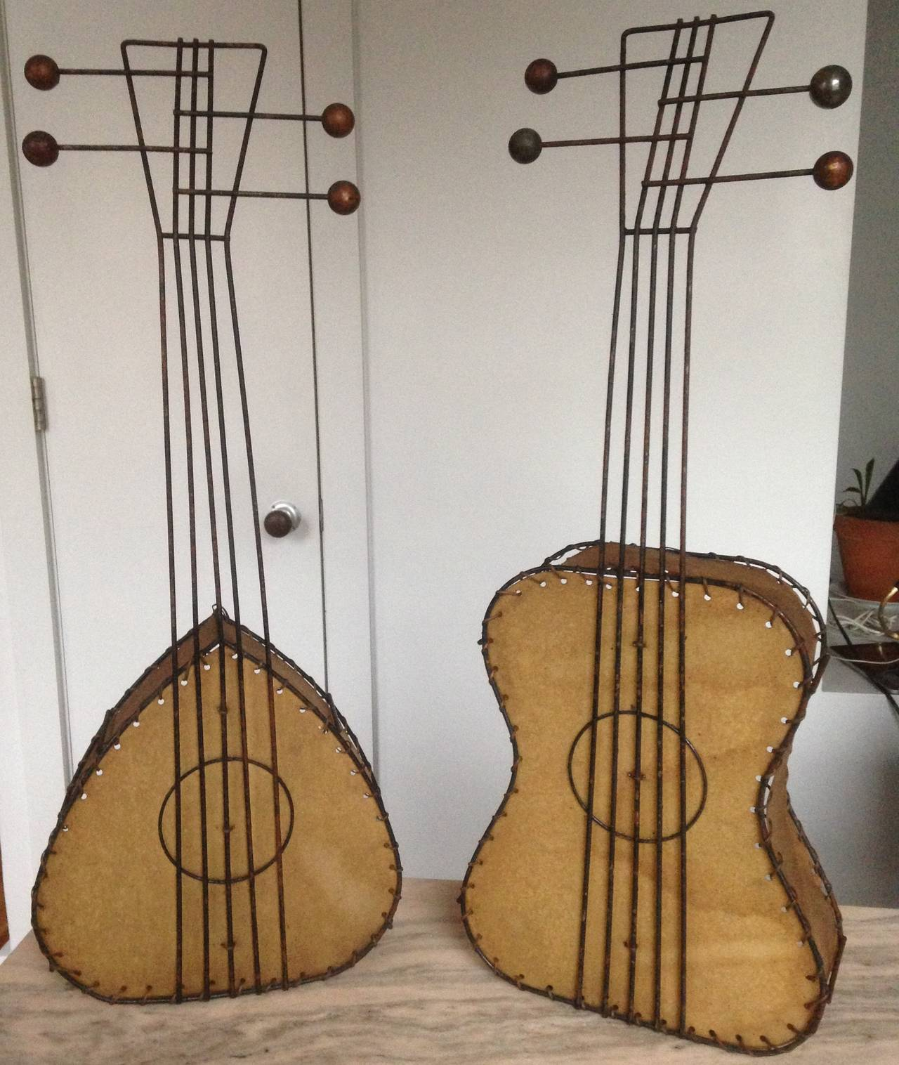 Table or wall lamps in the shape of a guitar and lute. Paper shade with metal frame with back-lit bulb with a Picasso-like sculptural sensibility.