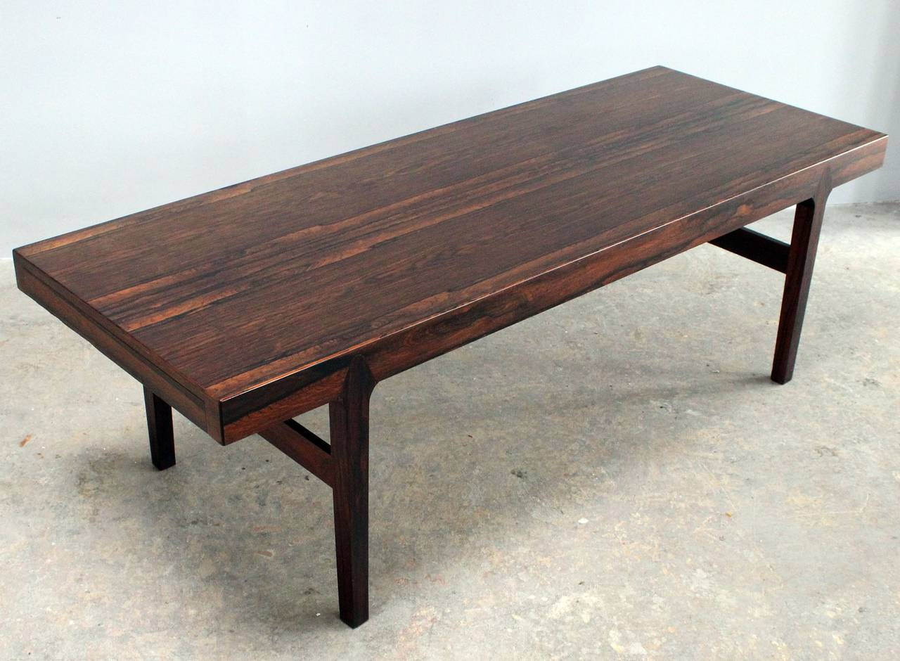 A bookmatched Danish, Brazilian rosewood coffee table with side extension and drawer and inlaid leg detail.