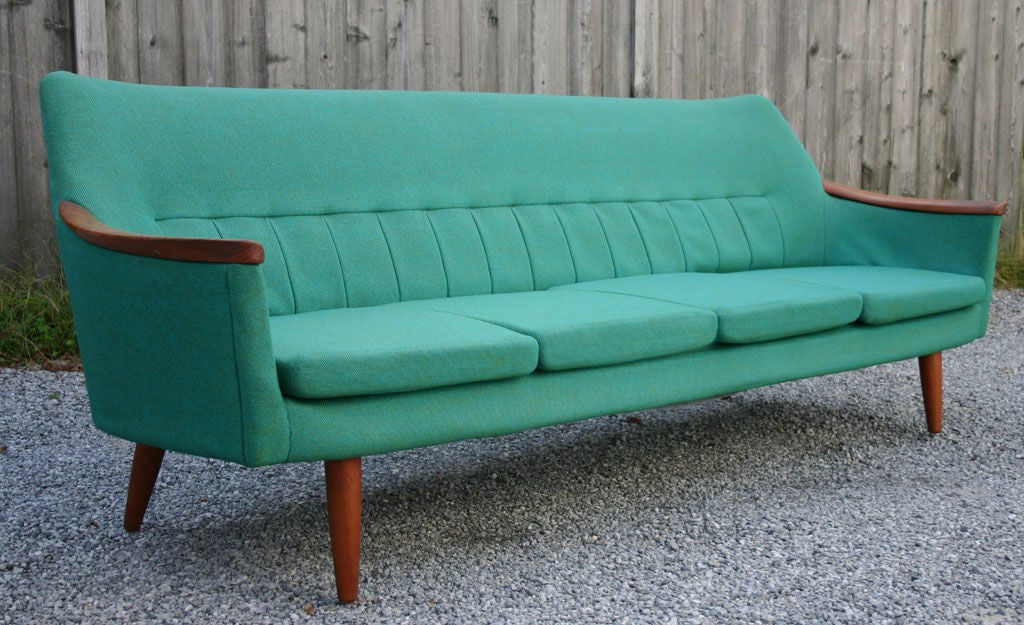 Svelte modern four seat sofa in teale upholstery with teak details.