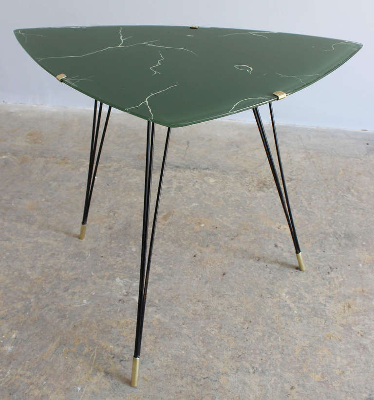 A leggy iron and brass frame side table with faux marble painted glass; and brass details.