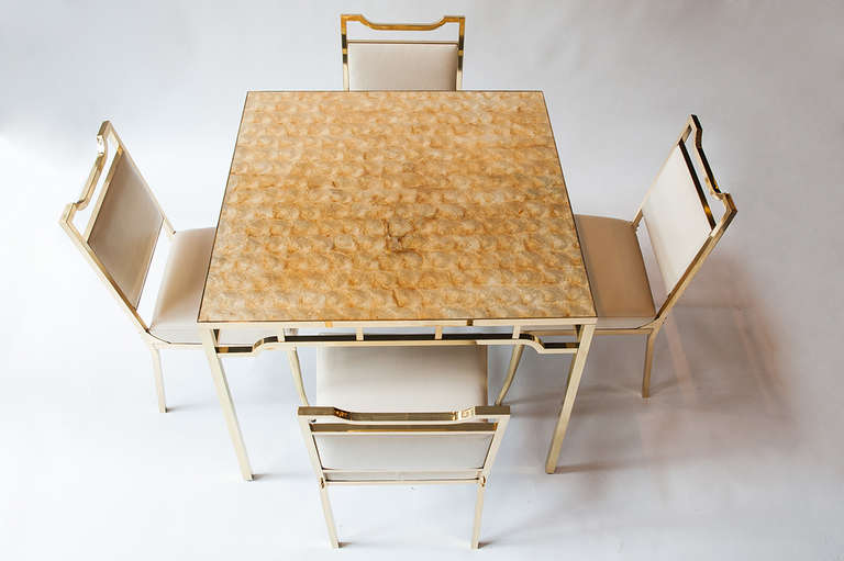 Beautiful brass table and chairs by Billy Haines, USA, circa 1950s. Table with inlaid capiz shell top. Chairs feature original cream vinyl upholstery and typical sabre style legs. Beautiful golden patina to tabletop.