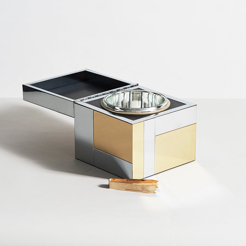 A rare ice bucket made in Paul Evans' signature Cityscape style. With its polished chrome and gold mirrored geometric parts, Evans' Cityscape series epitomizes the era in which it was made. The interior features a mirrored bowl and a pair of tongs
