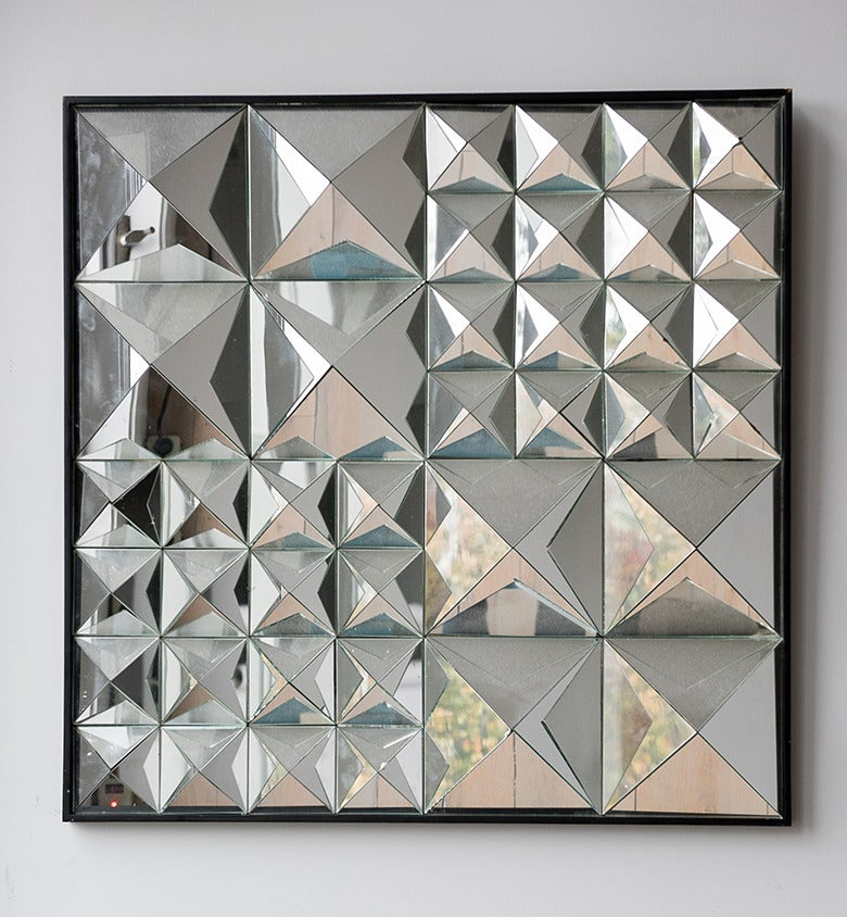 This rare wall-mounted mirror sculpture by Verner Panton from the 1960s is comprised of four quadrants of pyramidal mirrored glass, which rests inside a painted wooden frame. The piece is an extraordinary example of Panton's playful, geometric