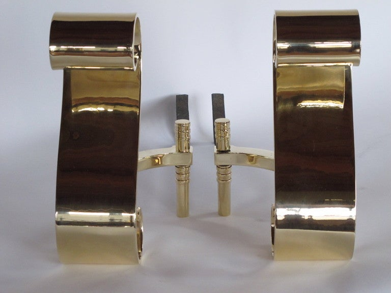 A pair of polished, heavy  brass, scroll shaped andirons.