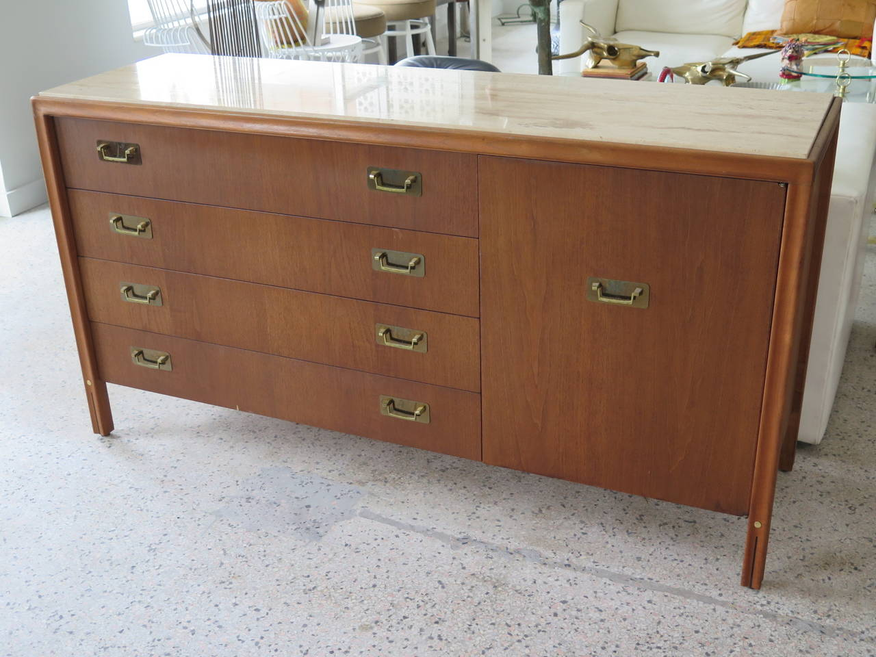 An unusual credenza by Gerry Zanck for Gregori I walnut with travertine top. Interesting brass handles and scalloped legs with brass detailing. Four drawers on one side and four smaller drawers with a door front. Finished on the back-so could easily