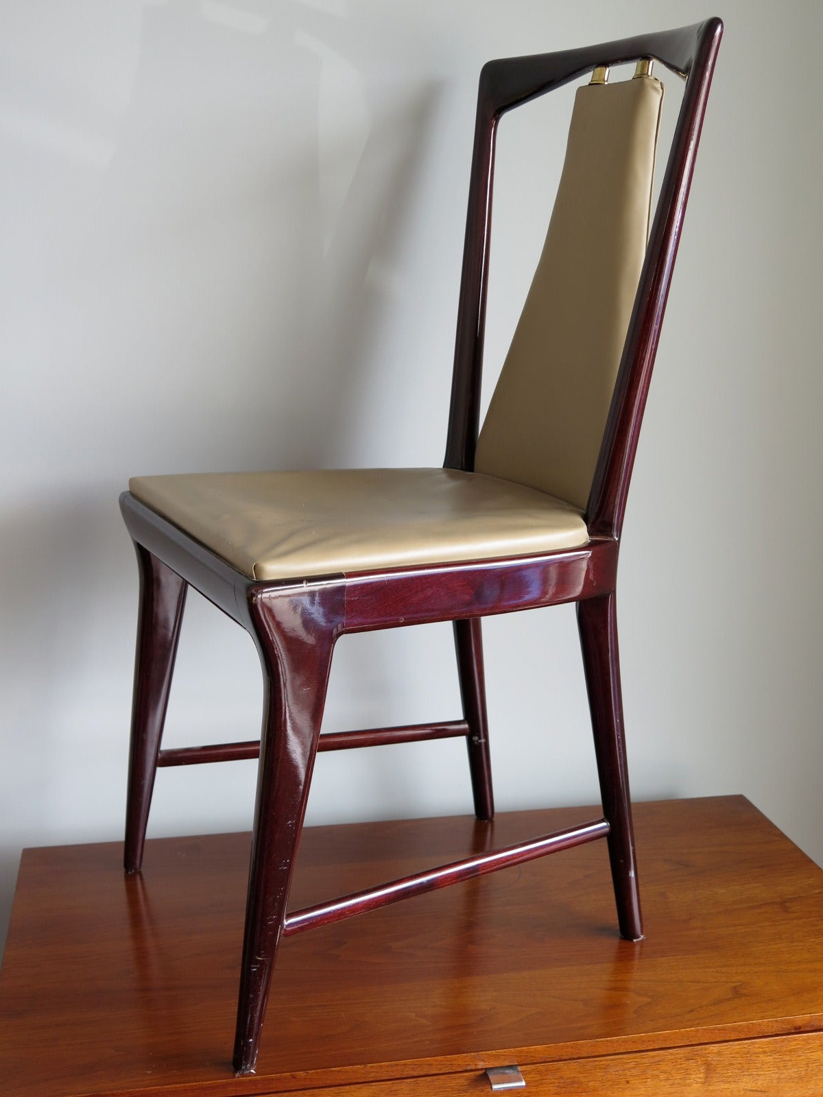 A set of 12 elegant dining chairs in the style of Osvaldo Borsani, Italy, circa 1955. Mahogany with brass details.