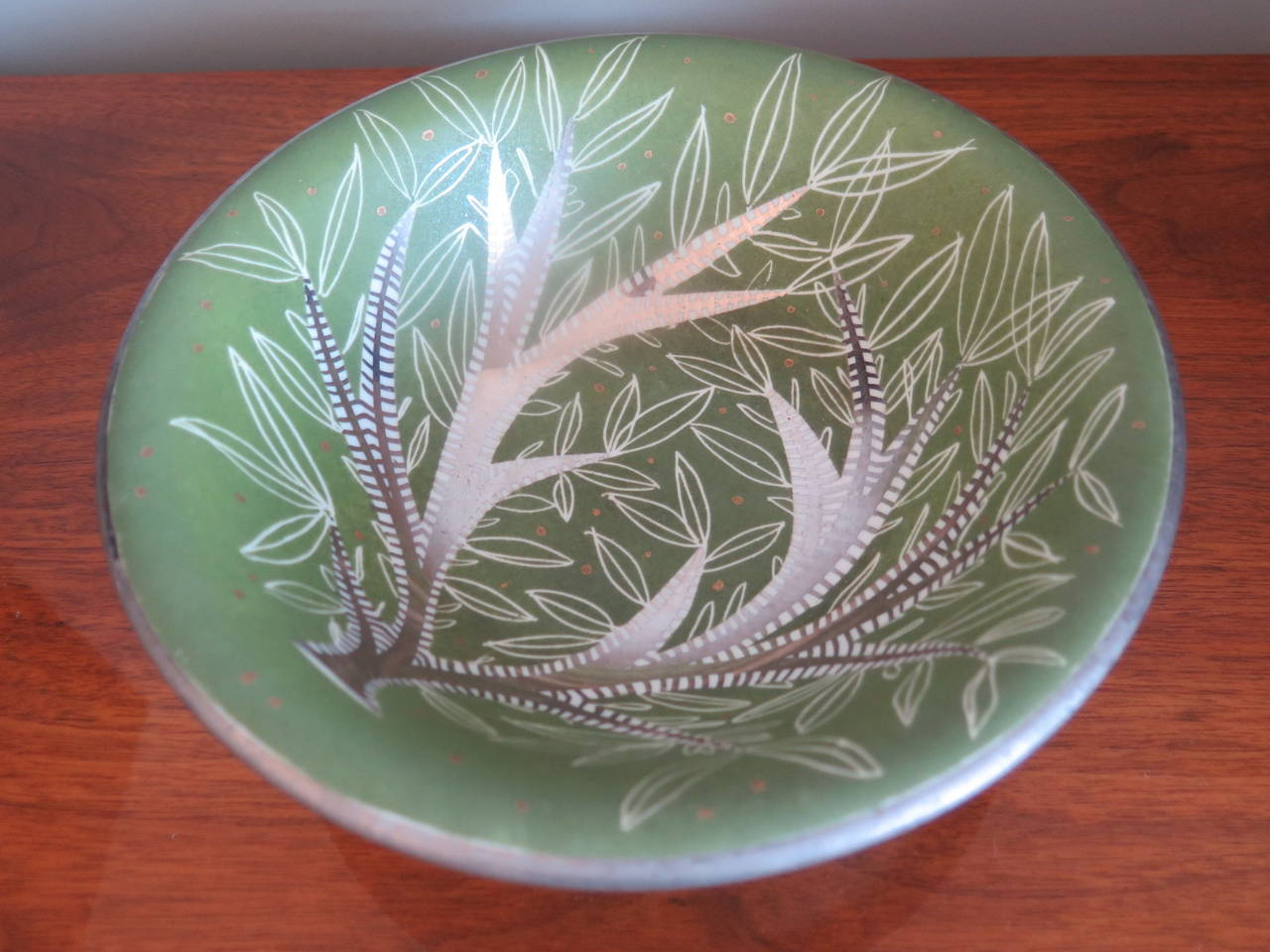 An elegant, hand painted bowl by Waylande Gregory. Stylized leaf pattern in green and silver leaf.