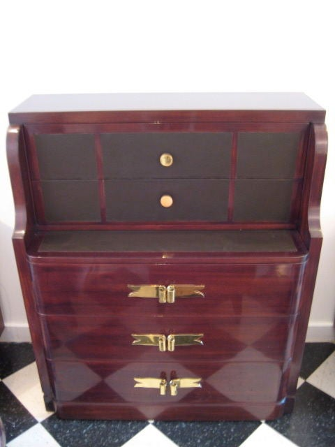 An elegant chest of drawers with pull-out desk drawer by Grosfeld House.