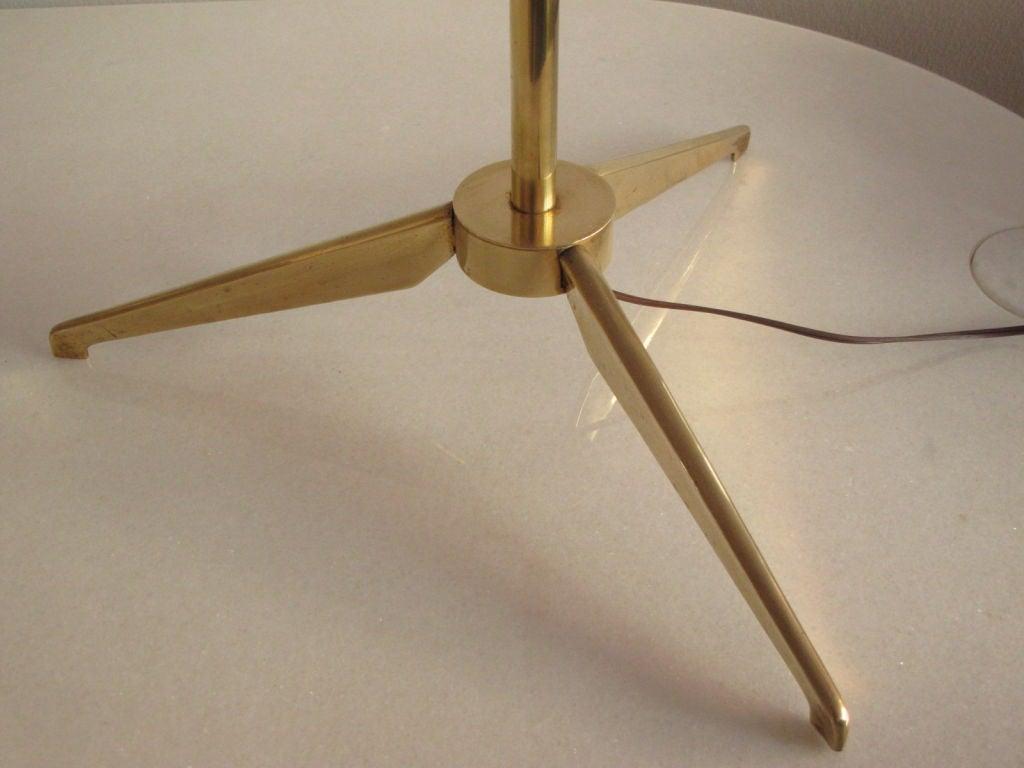 An elegant brass torchere by Stilnovo (Italy), ca' 1950's. Tripod base, oplaine glass shade with brass trim.